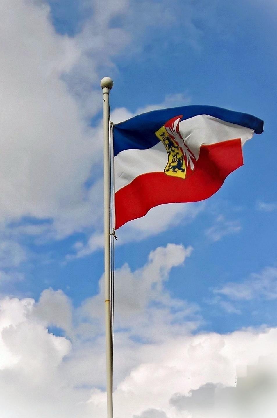 Wehende Flagge Schleswig-Holsteins vor leicht bewölktem Himmel