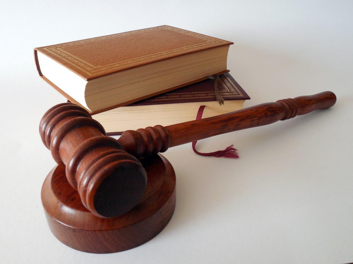 hölzerner Richterhammer und zwei Gesetzbücher auf weißem Tisch