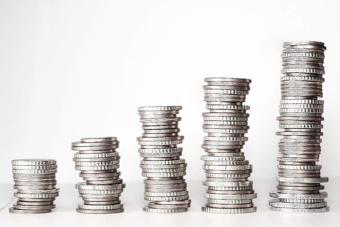 fünf Stapel mit silbernen Münzen vor weißem Hintergrund