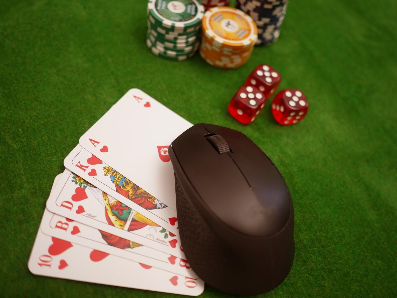 Computermaus, Spielkarten, Pokerchips und Würfel auf grünem Pokertisch
