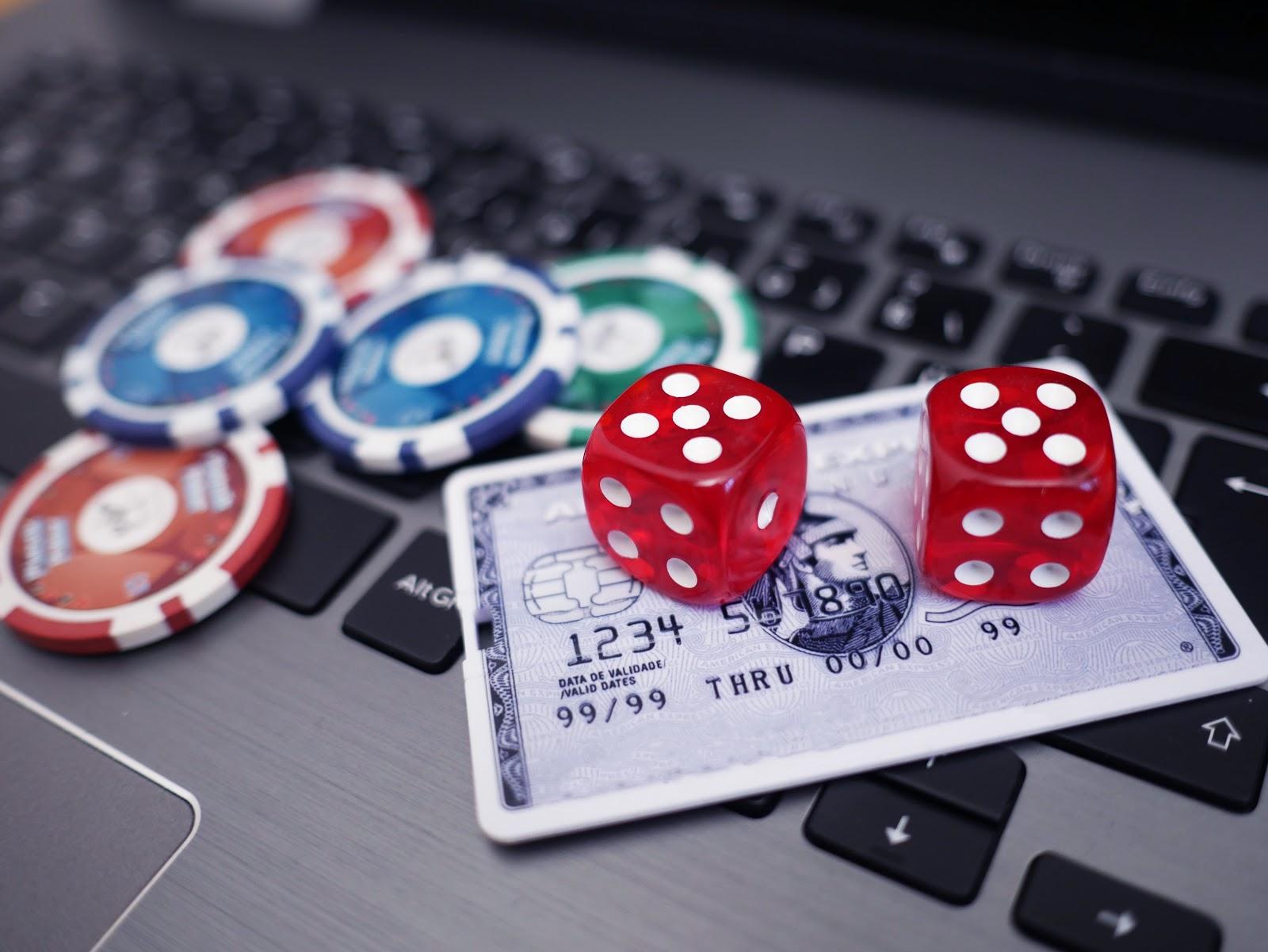 Pokerchips, rote Würfel und Kreditkarte auf einem grauen Notebook