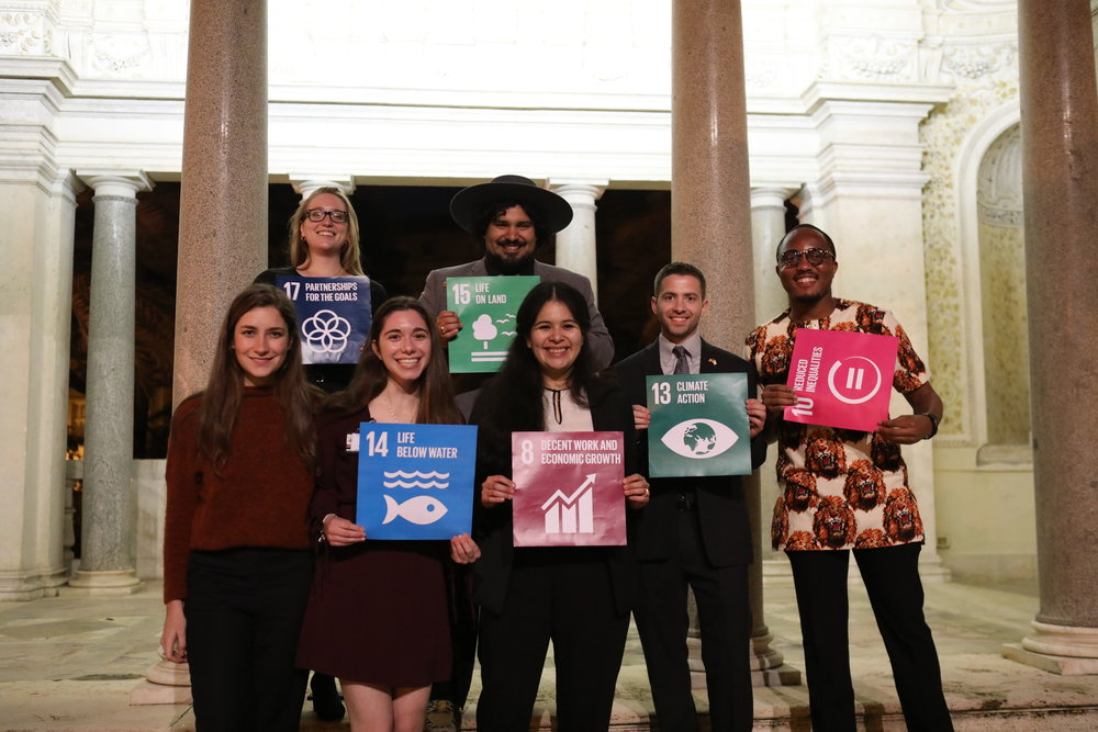 Seven of the eight returning participants pose together at the Global Village Dinner & Drinks. From left to right - top - Molly Burhans and Clayton Ferrara. From left to right - bottom - Mariana Ruenes, Sienna Nordquist, Gabriella May Lagunes, Anthony Bucci III, and Obinna Nnewuihe.  Photo Credits: Yuntong Man/SDSN Youth