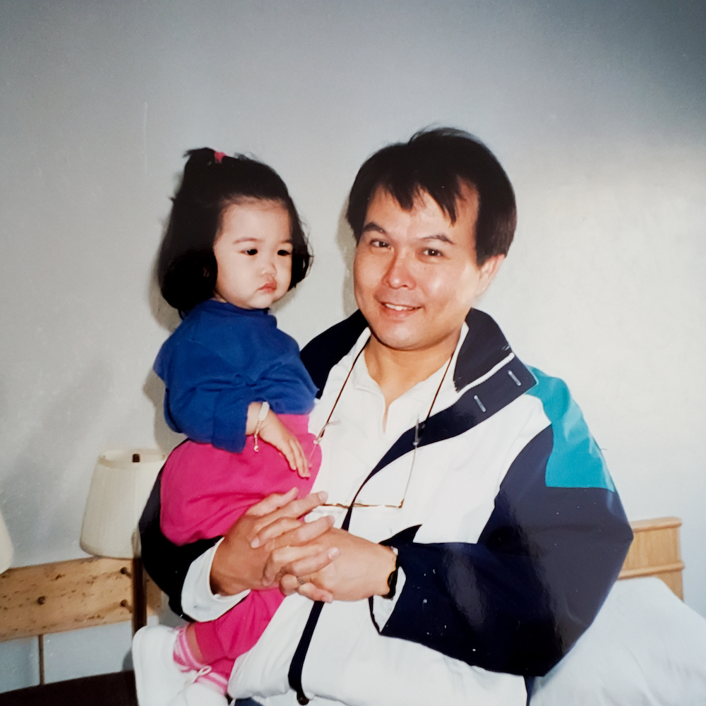 Ada, as a toddler, being held by her dad, who is wearing a very 80s/90s style windbreaker