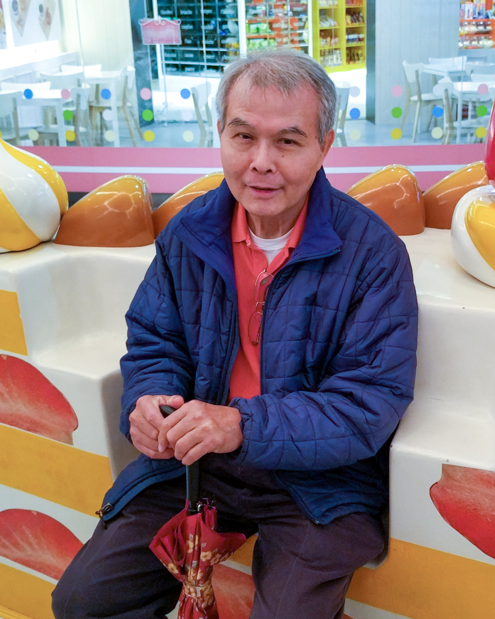 Ada's Dad, Yuan, sitting on a bench shaped like a slice of cake, while holding a cane