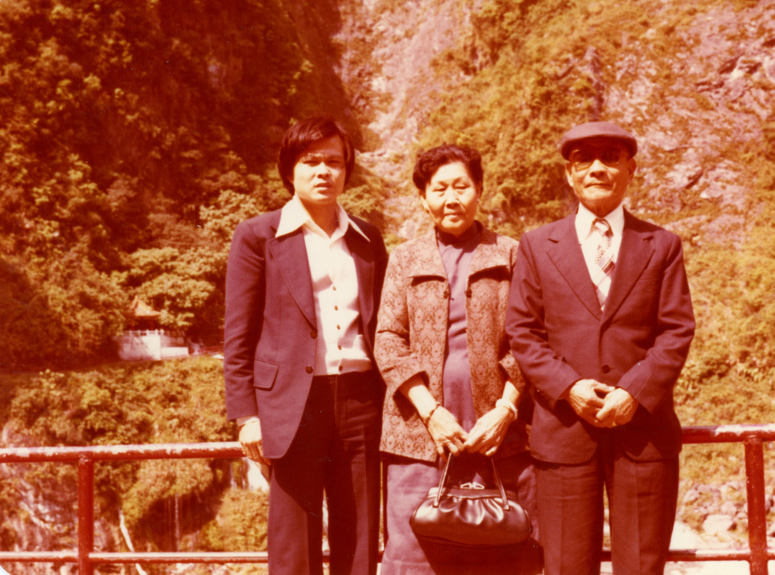 Ada's Dad, in the late 70s or early 80s, with his parents, wearing formalwear and standing on a bridge
