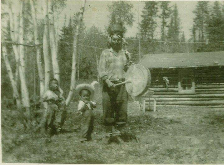A scan of an old photograph depicting a figure with a drum alongside two children in front of a log cabin.