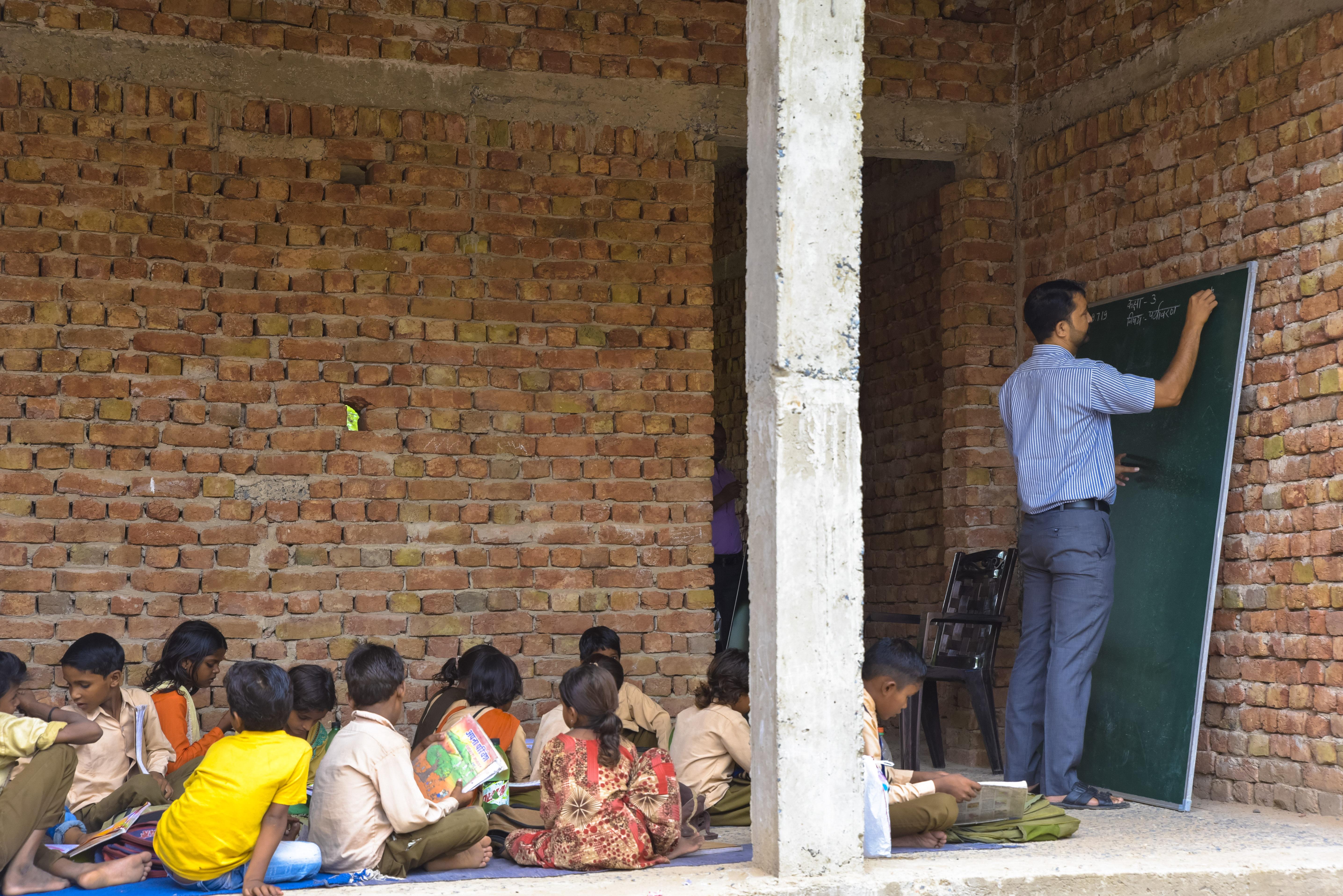 A teacher teaching in an under-construction classroom