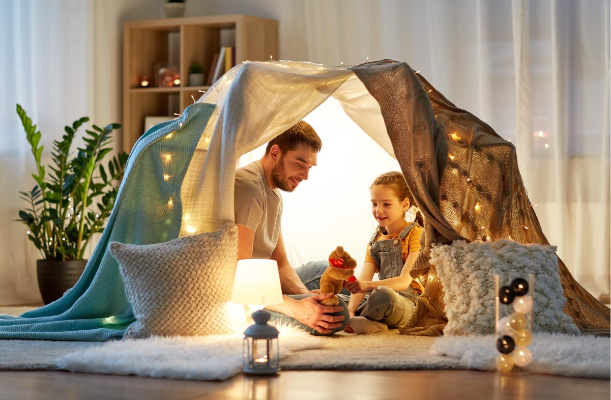 a father and daughter inside a homemade den