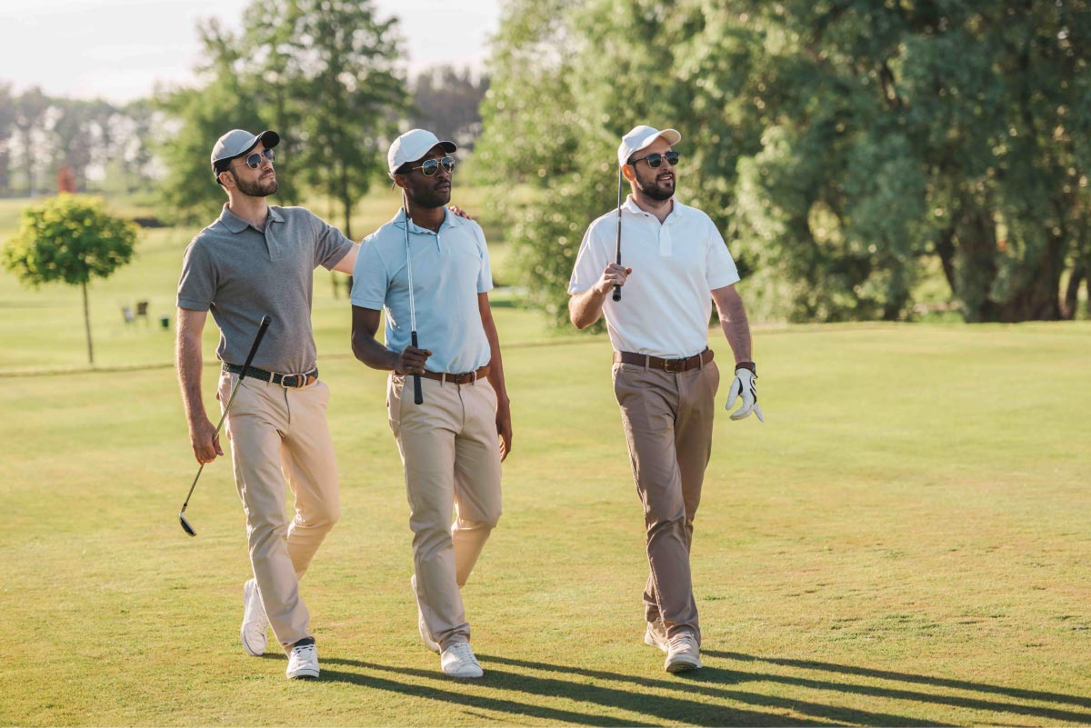 three men with golf clubs walking on a golf course