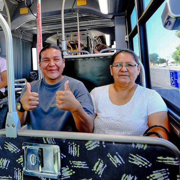 Pasajeros sonriendo abordo en transporte público