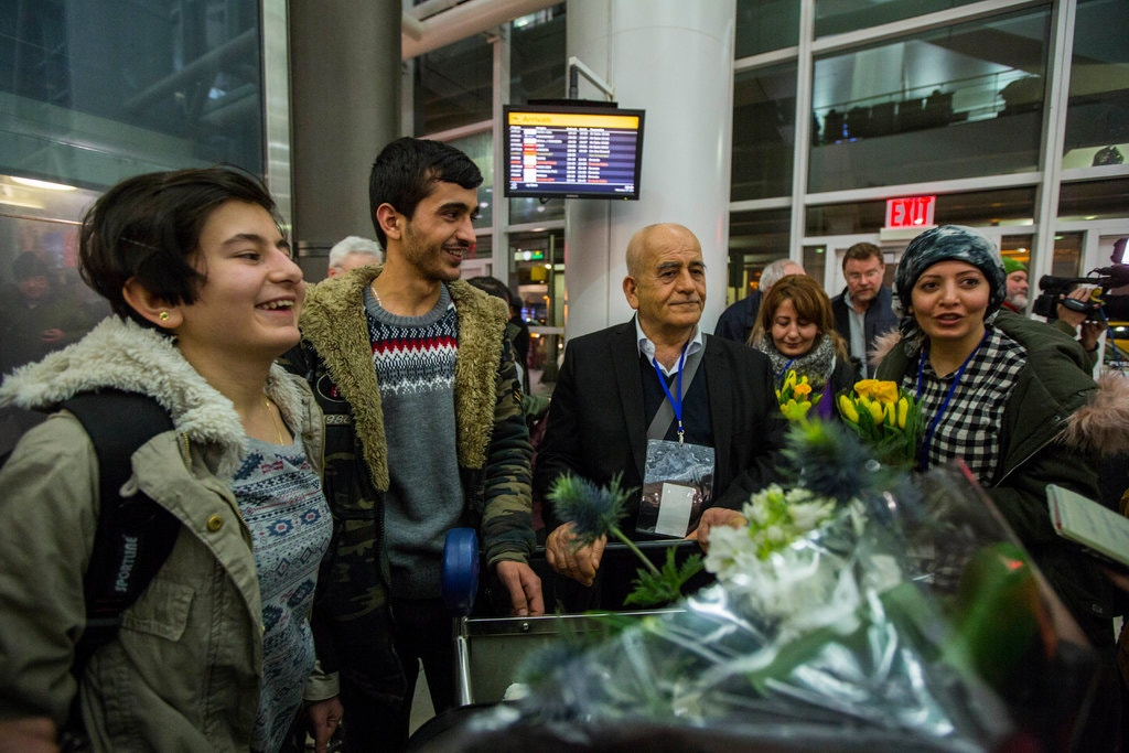 Members of the Khoja family being welcomed at Kennedy International Airport. Photo courtesy of Hiroko Masuike/The New York Times.
