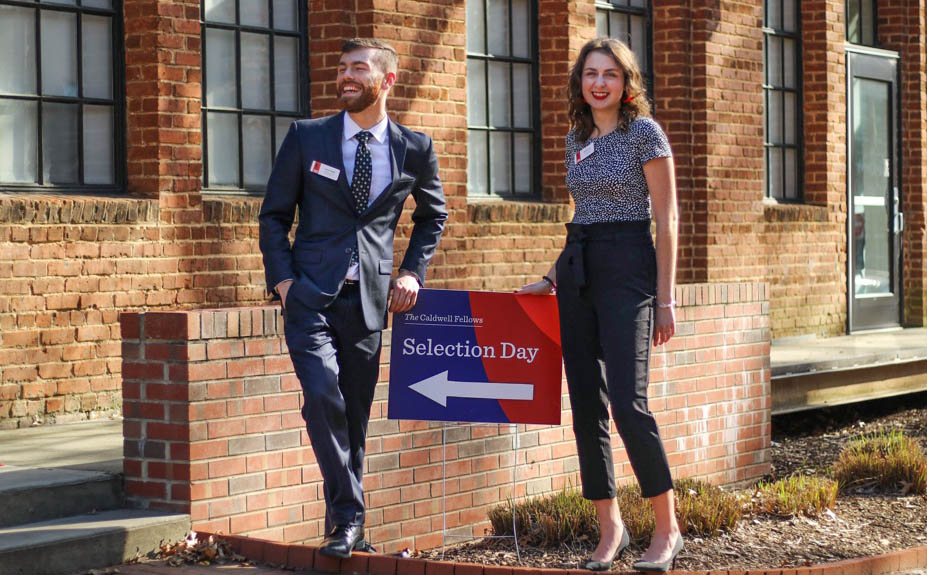 Jack and Maggie standing next to a Selection Day sign in front of Park Shops.