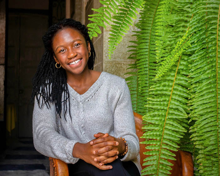 Anu Frempong smiling next to a plant.