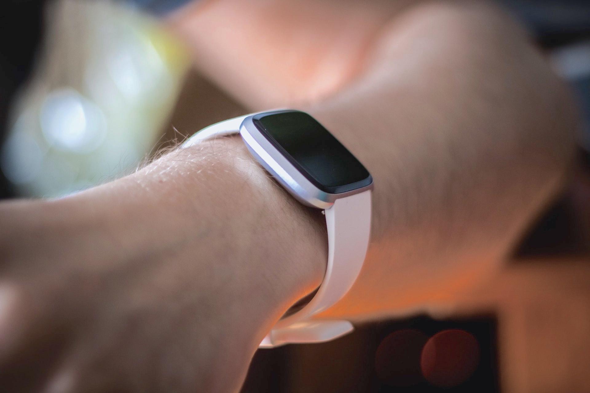 A user's wrist wearing a Fitbit smart watch.