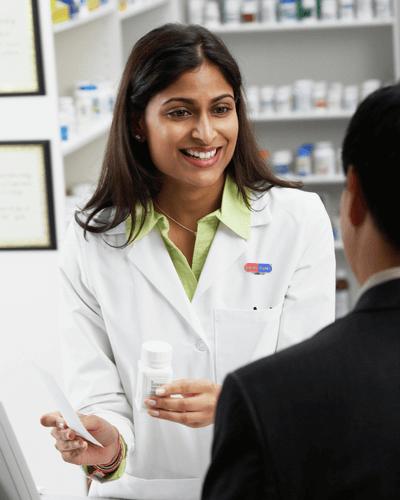 Drug Mart pharmacist helping customer at counter