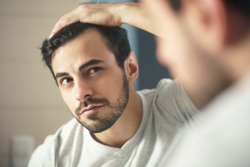 A man looking at hair in the mirror.