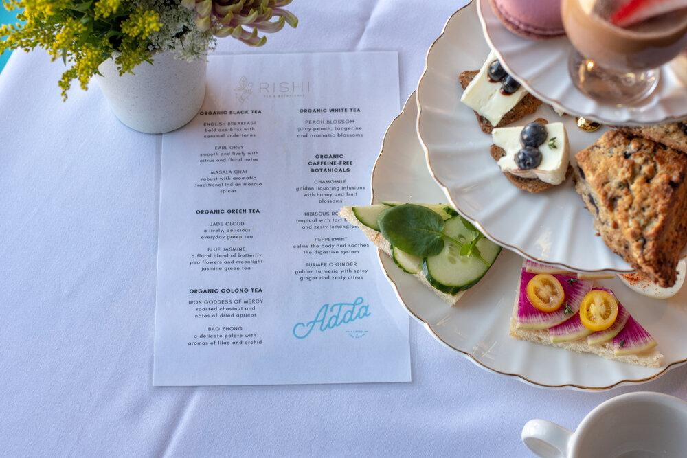 A table with a tea menu and snack platter