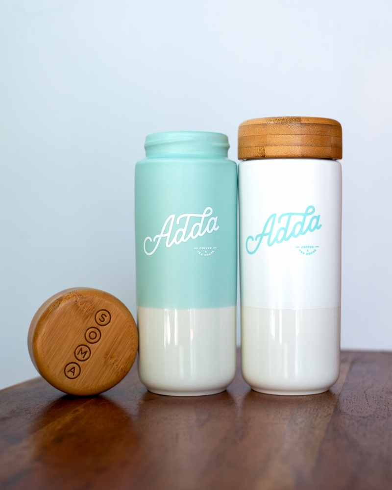 Two white and blue Adda x SOMA ceramic bottles with a bamboo twist on lid