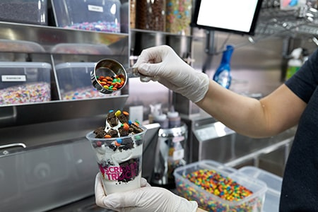 A worker selects tasty toppings for a treat.