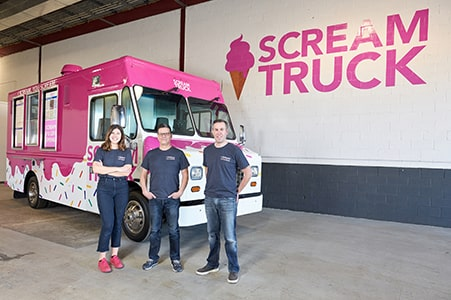 The founder of Scream Truck and his employees stand in front of the truck.
