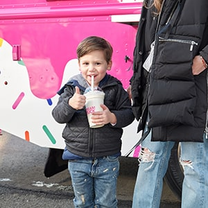 A boy smiles and gives a thumbs-up while eating ice cream.
