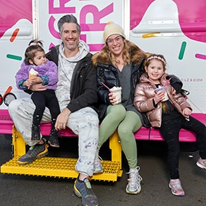 A happy family sits on the back of an ice cream truck.