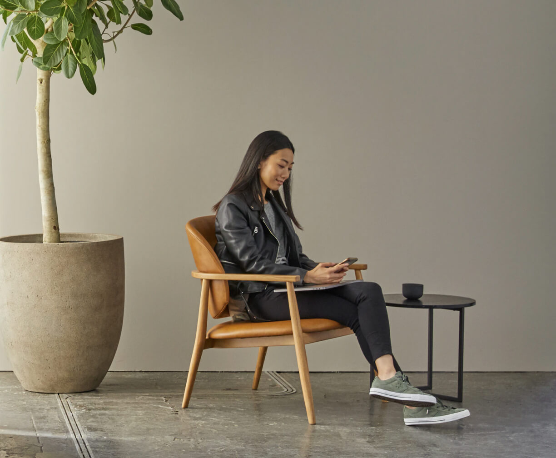 wanita sedang duduk dan melihat handphone