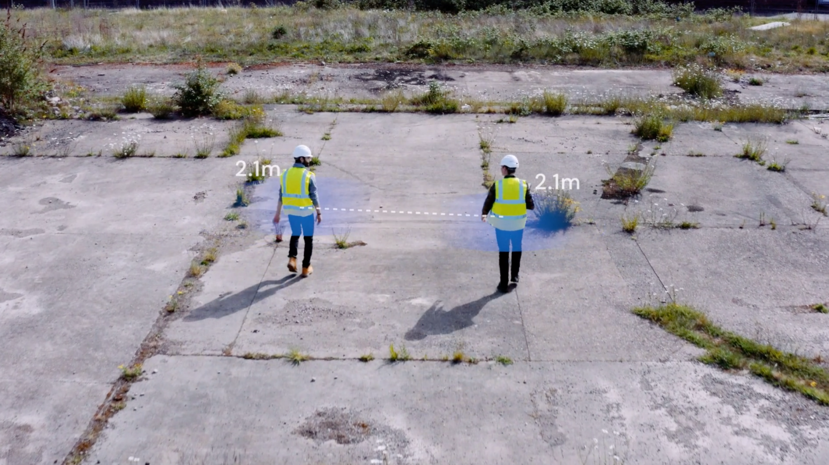 Two people wearing PPE on a building site walking at a distance of 2m apart to maintain social distancing.