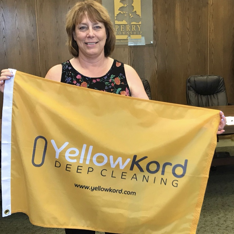 A happy customer holding Yellow Kord flag