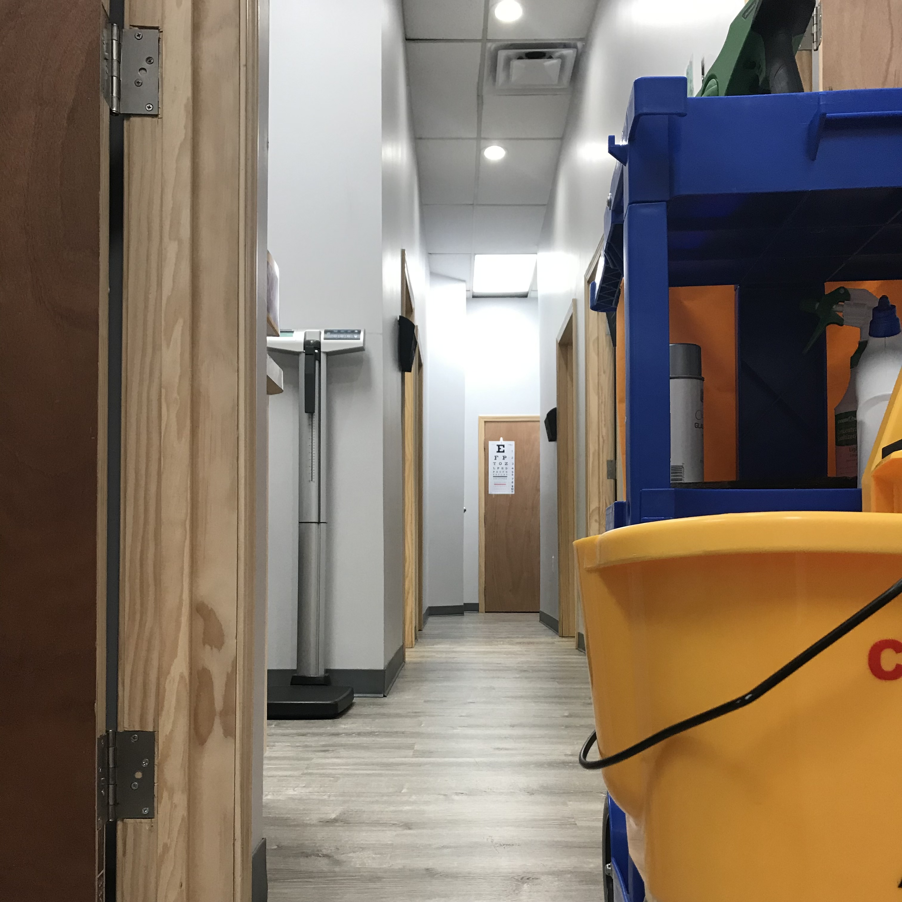 A Yellow Kord janitorial cleaning cart in the hallway of a medical office
