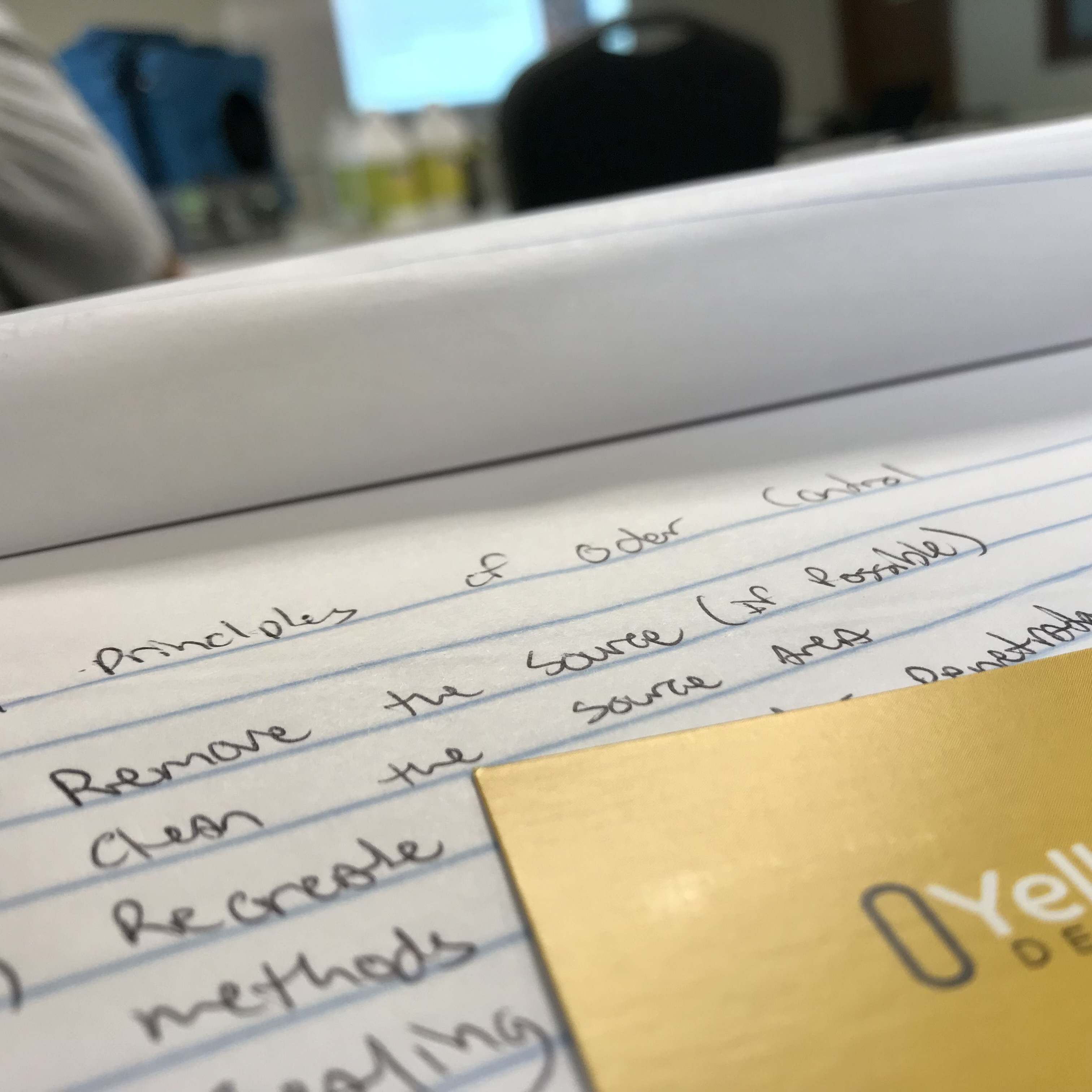 A note pad including the principles of odor control with Yellow Kord business card