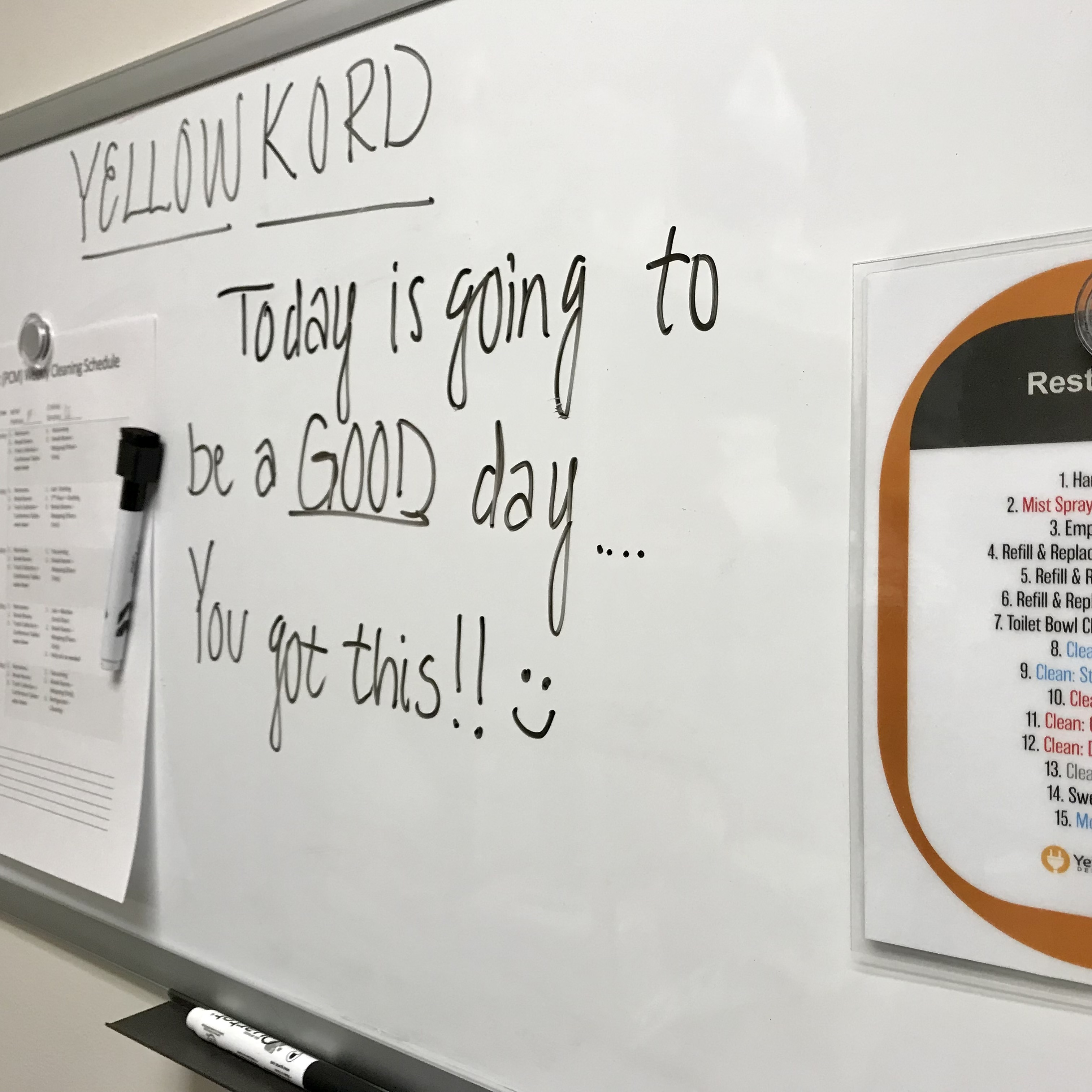 A dry erase board holding up employees schedule and cleaning task cards at Yellow Kord
