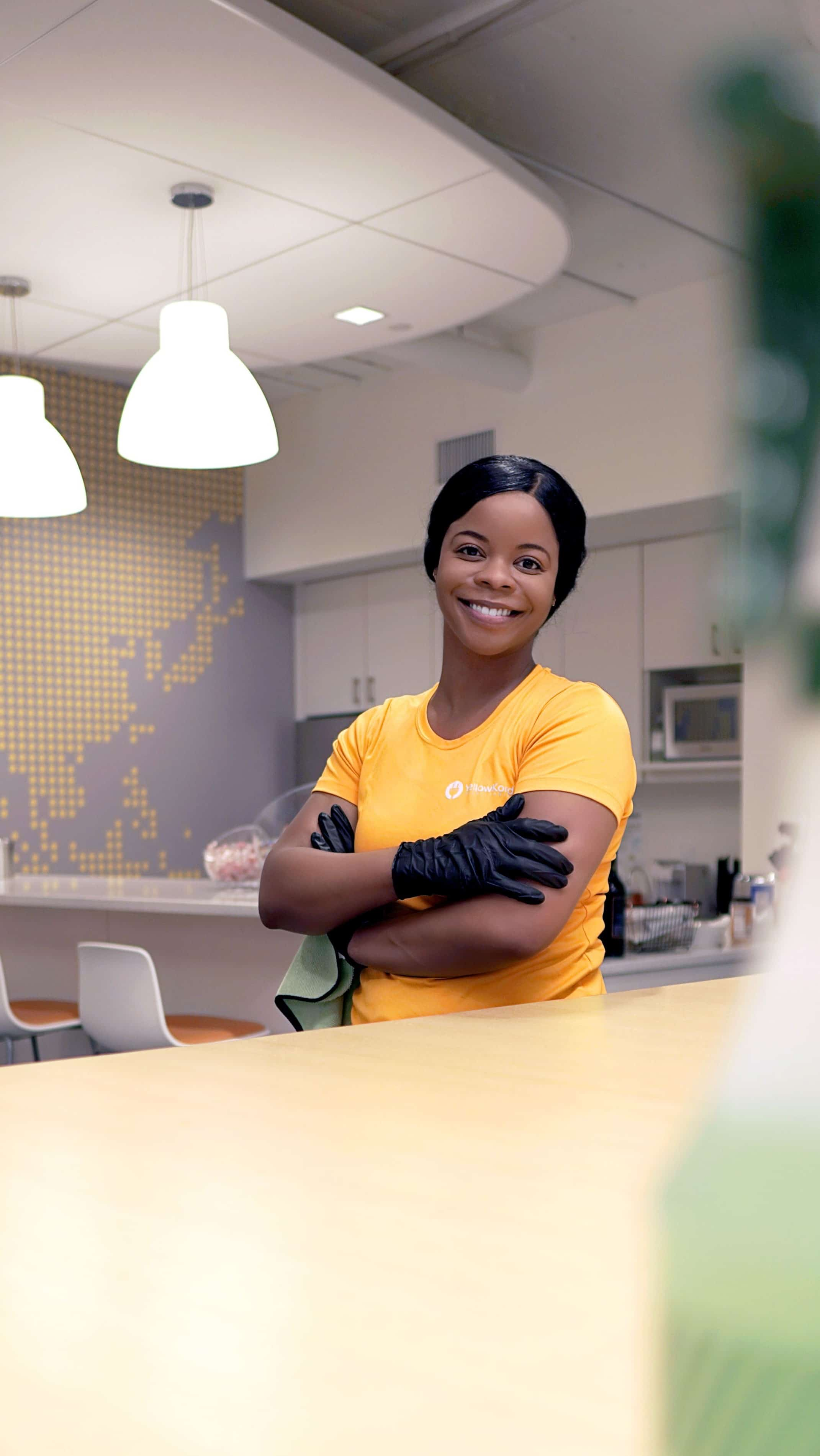 A Yellow Kord employee smiling after finishing her cleaning task