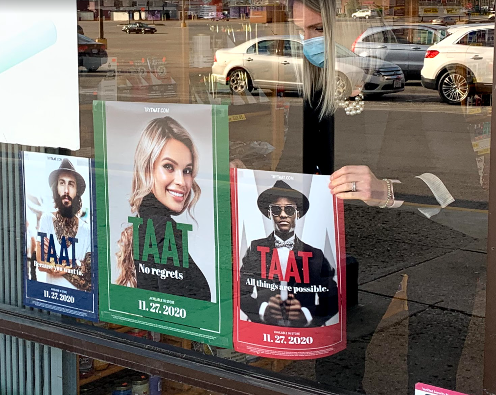 Promotional in-store graphics being placed in the window of one of Taat's retail points of sale in Ohio.