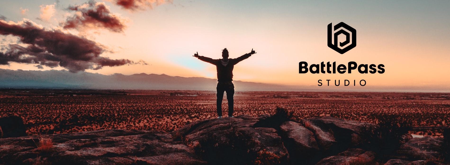 BattlePass studio banner, man stands towards sunset