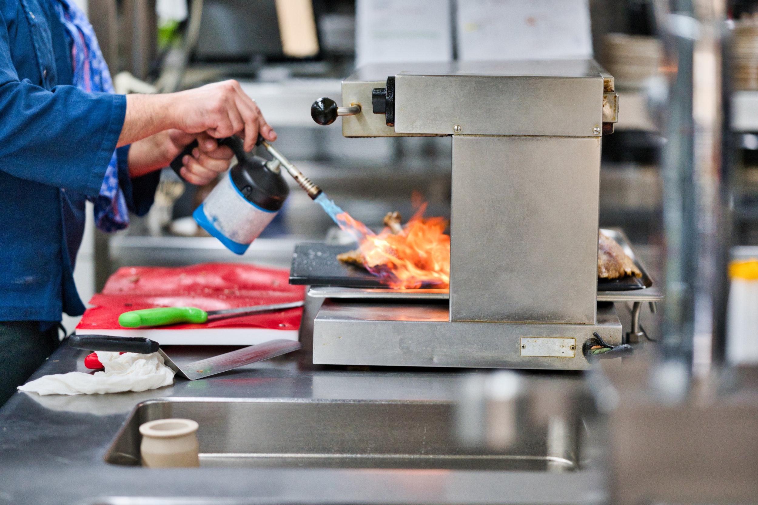 Restaurantküche beim flämmen einer Gans