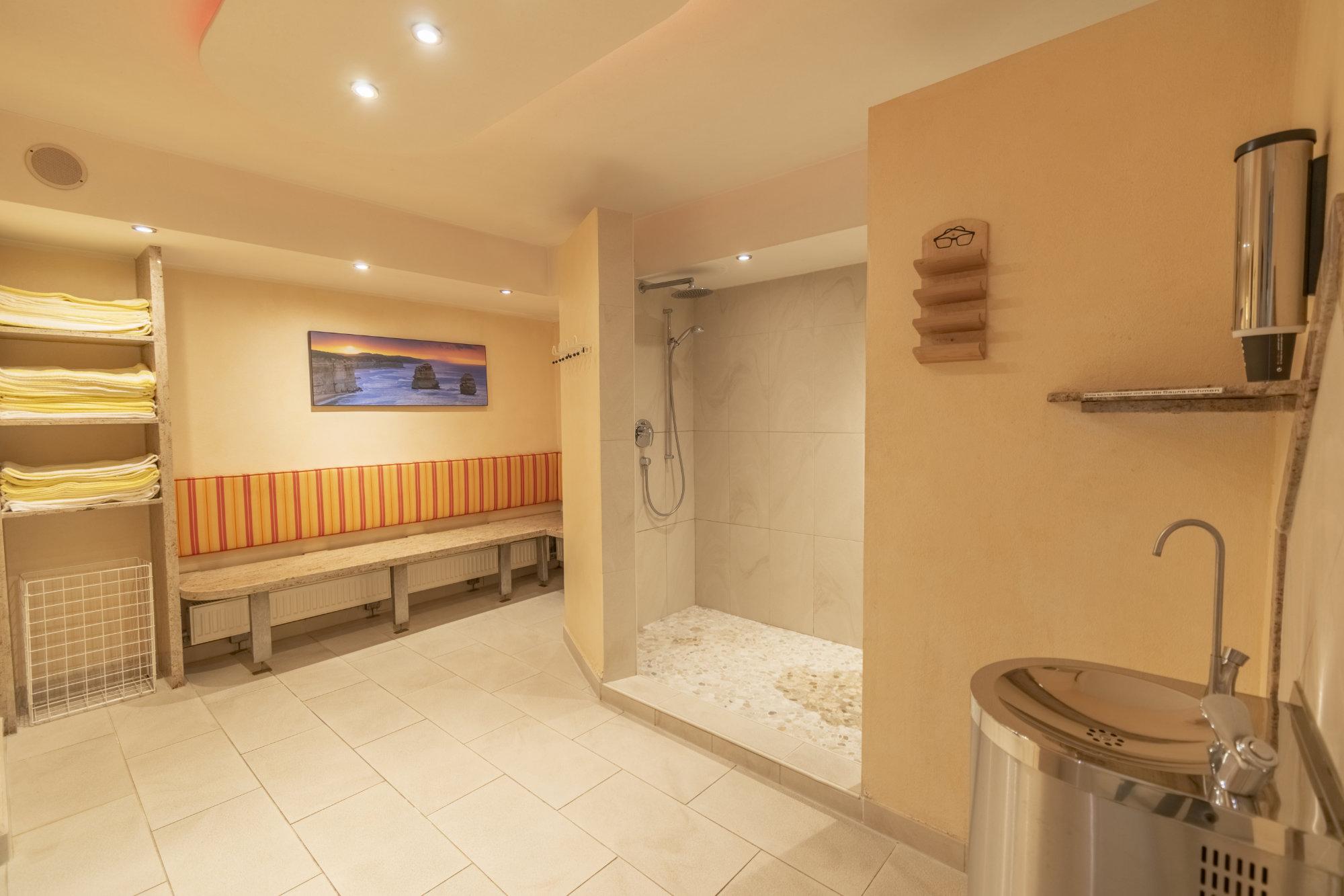 Außenbereich vor der Sauna mit Duschen und Trinkbrunnen