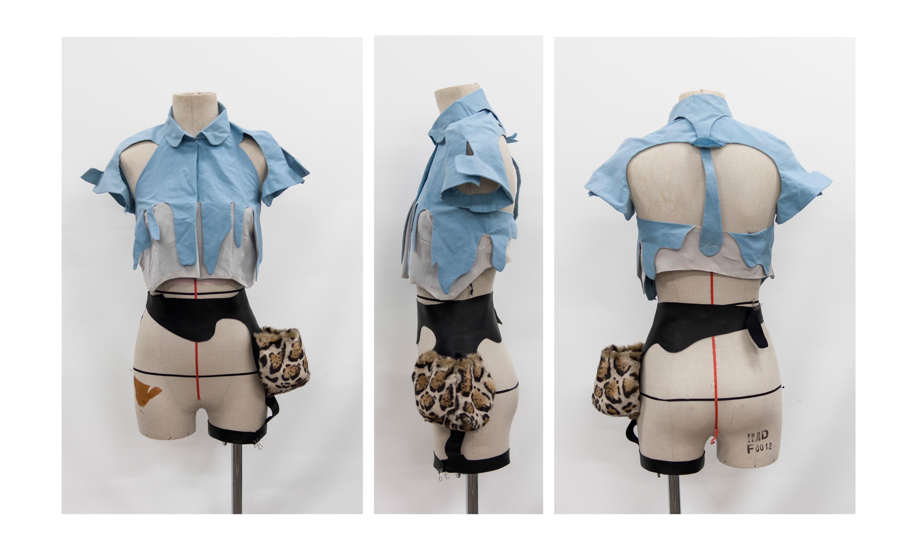 a mannequin wearing a leather and faux-fur hip bag with a leg strap, and the two-tone muslin for the surrealist blouse, the upper half of the blouse is blue, the lower half is grey, which pronounces the drip shape of the bust seam.