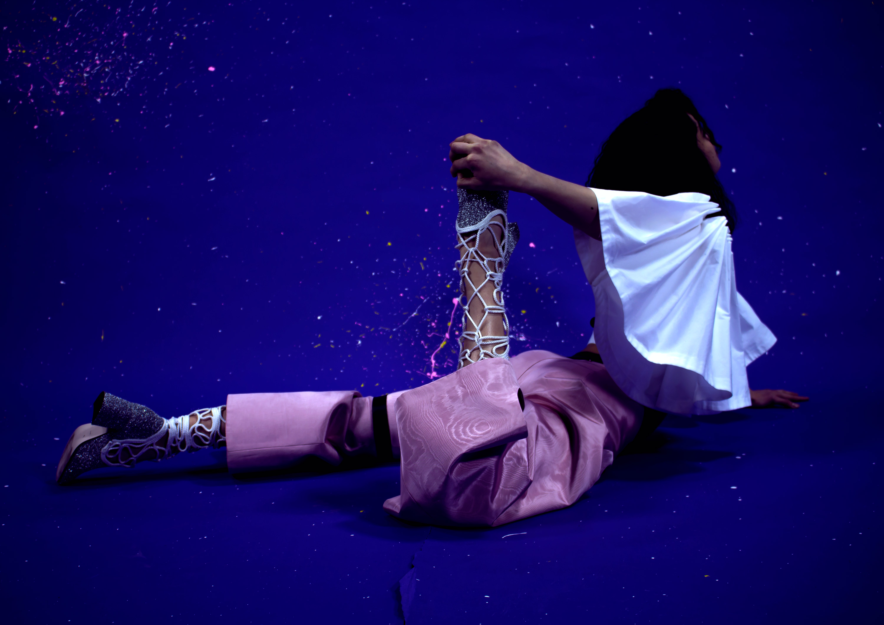 Low-lit photo of model wearing pink moirée disco pants, glitter boots and dali at the disco white shirt-blouse