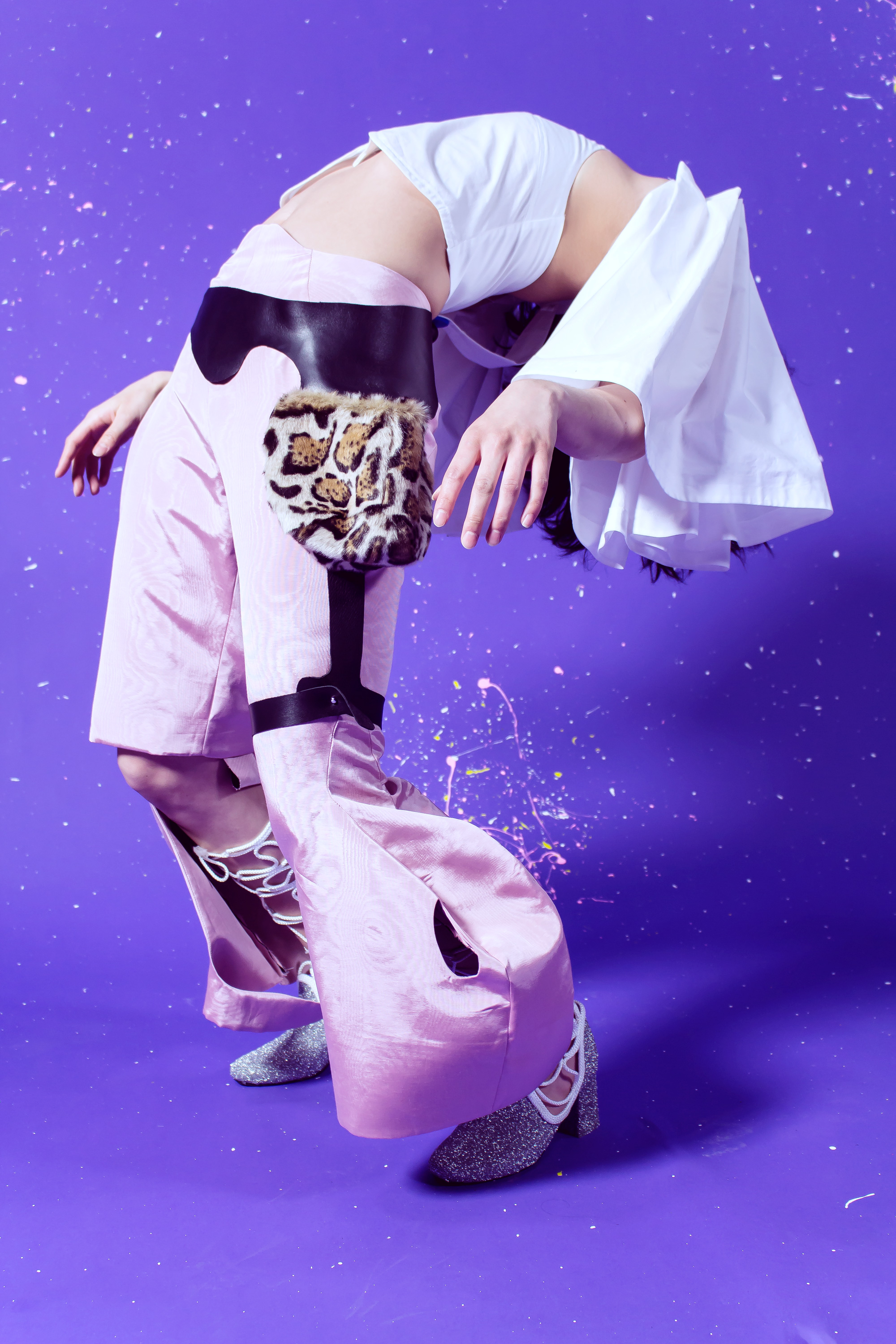 Model wearing Dali at the Disco white cotton blouse, pink moirée cut-out pants, ocelot belt and glitter boots while bending over backwards in front of a purple studio background