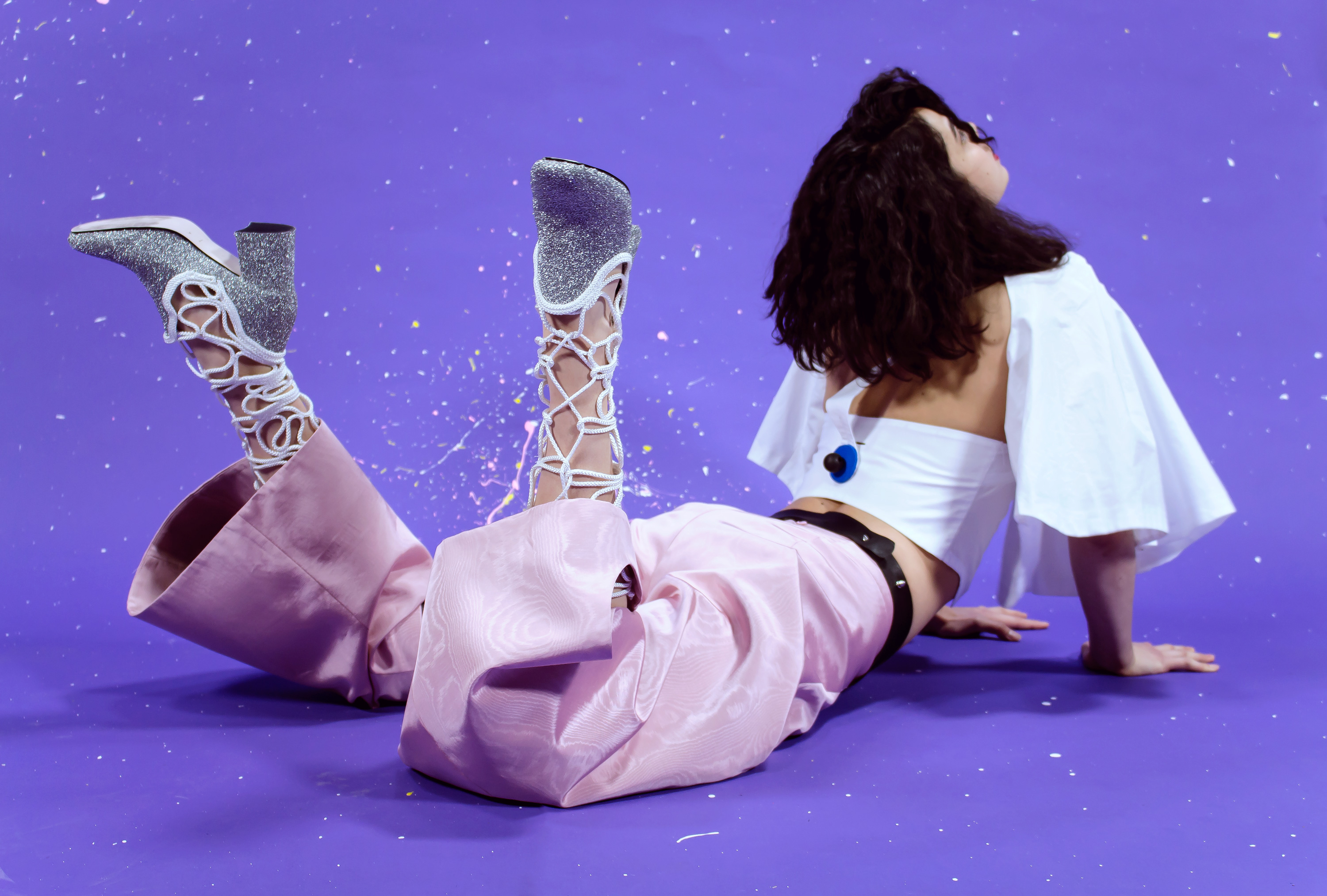 Model on ground in upward facing dog pose with feet and face raised to the ceiling, wearing Dali at the Disco white cotton blouse with big sleeves, pink moirée cut-out pants, ocelot belt and glitter boots