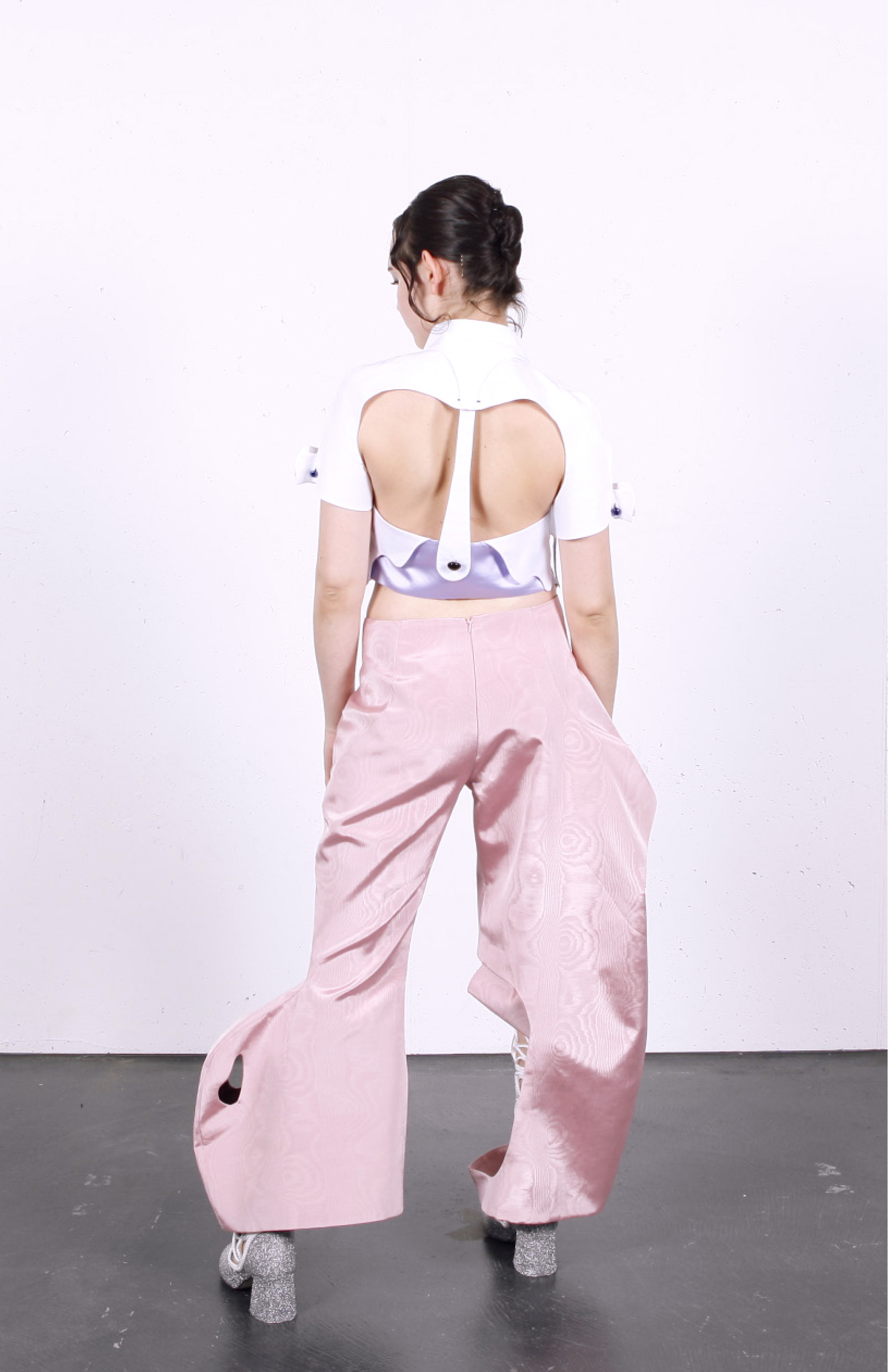 Look 1 consisting of surrealist blouse, pink moirée disco pants, glitter boots and ocelot belt bag, back view