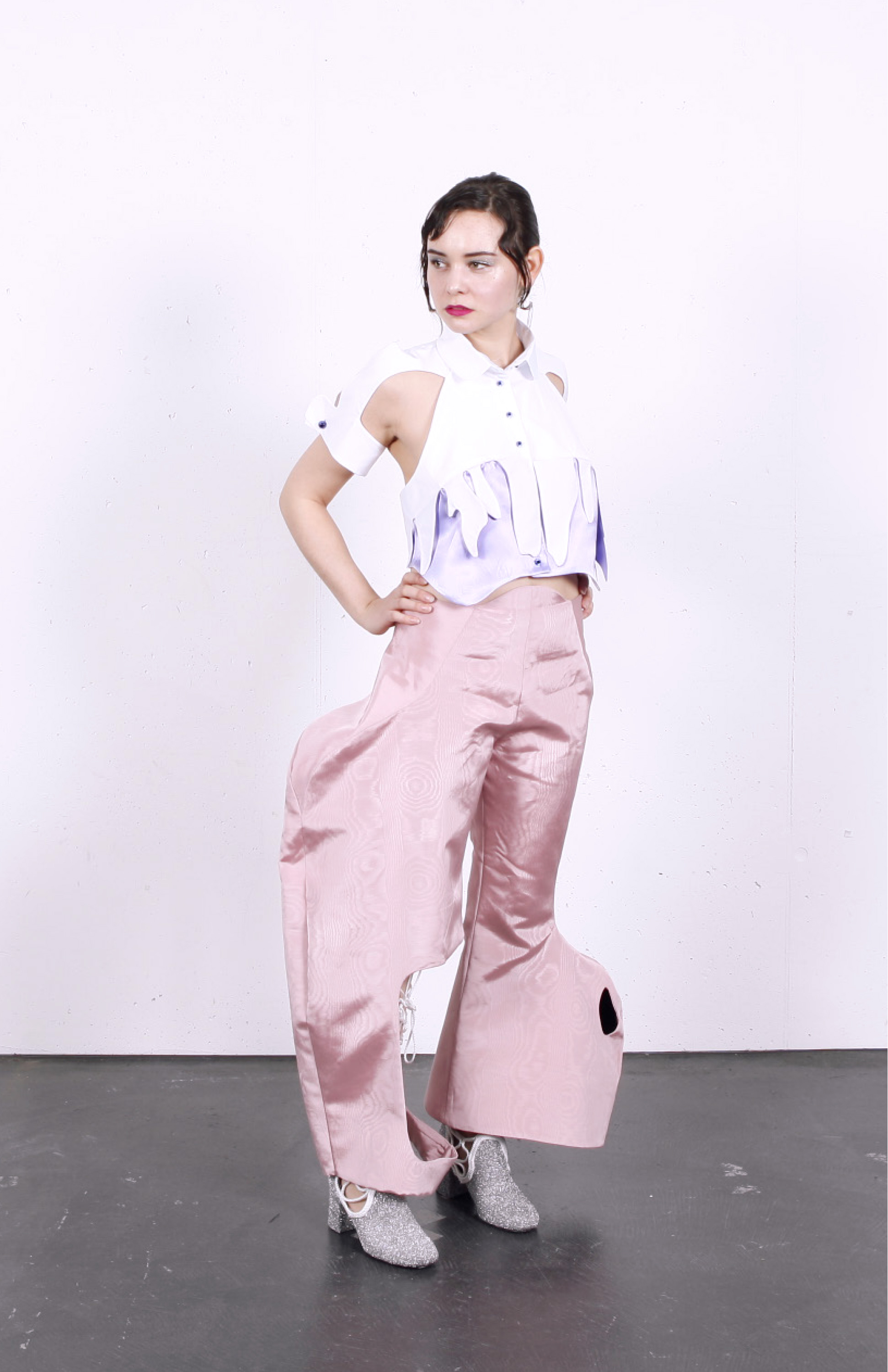 Look 1 consisting of surrealist blouse, pink moirée disco pants, glitter boots and ocelot belt bag, front view