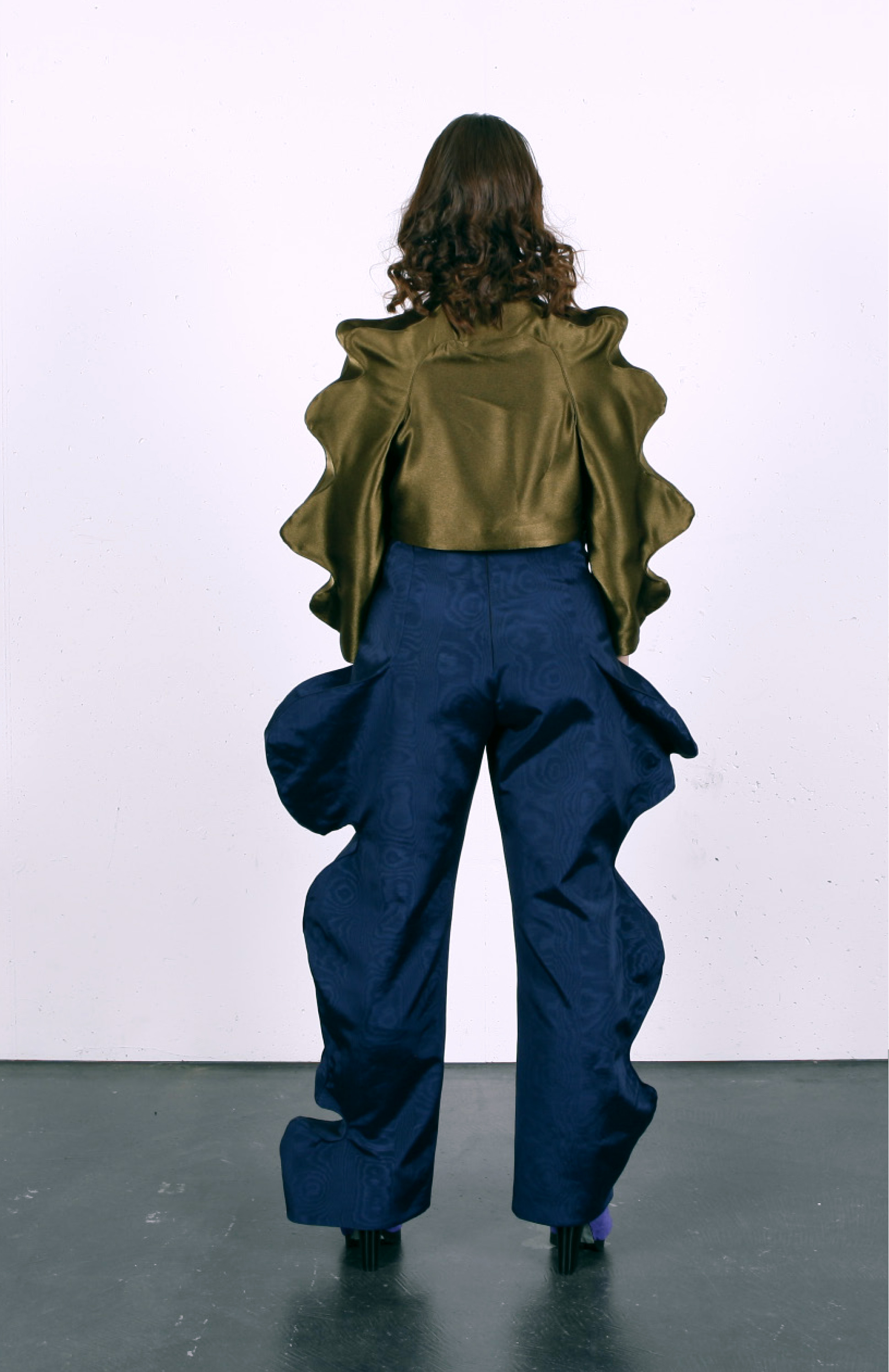 Look 2 consisting of blue jumpsuit, green silk jacket and purple and mint suede boots, front view
