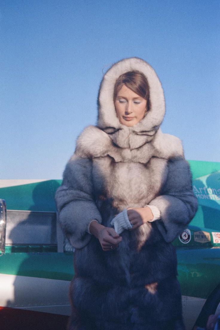 Nina Rindt standing in front of a green race car and blue sky in a pale grey fur coat. Photo from the late 1960s.
