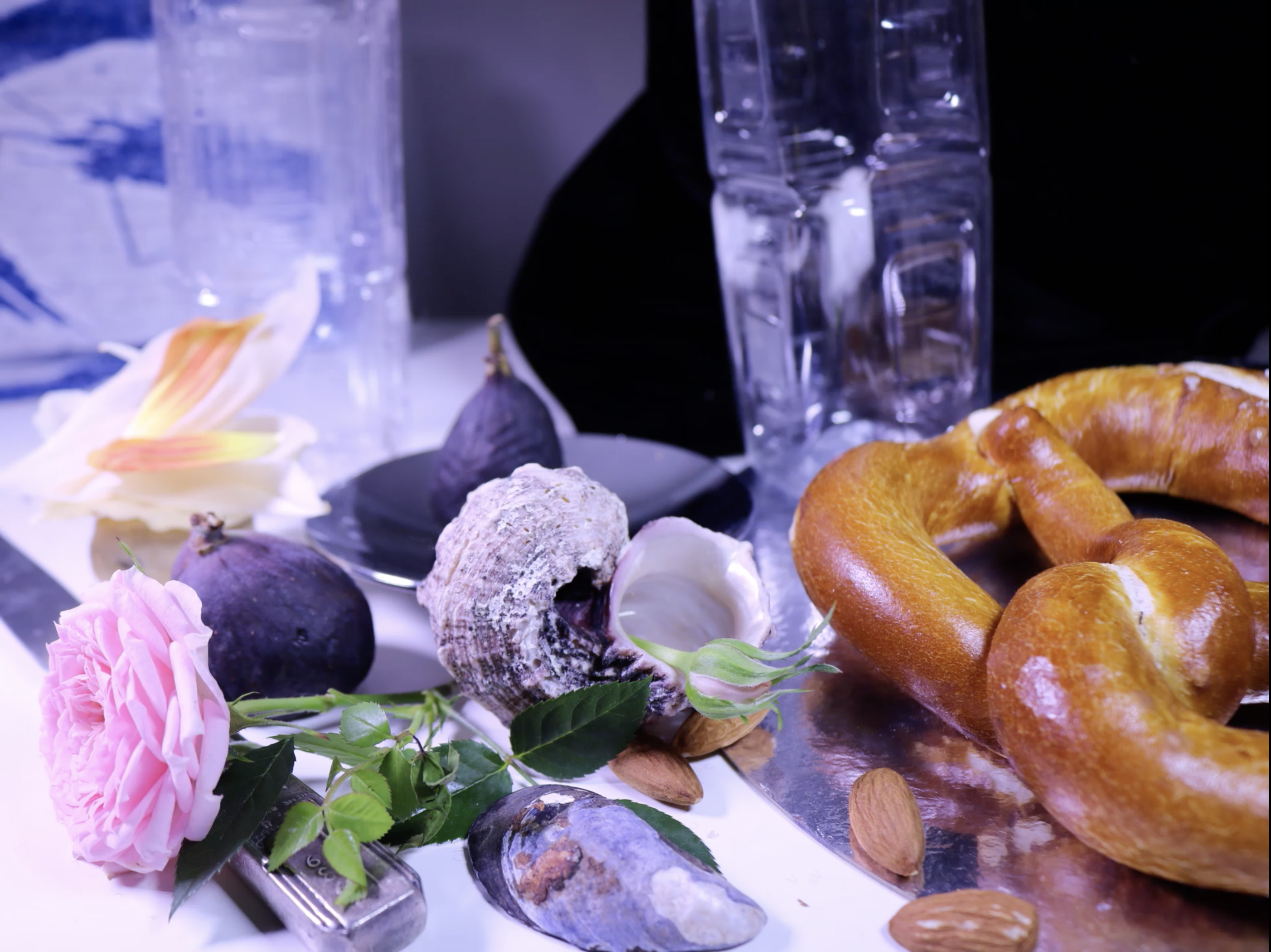 A still life composition that includes a pretzel on the right hand side side of the image, on a table with a few almonds, a pink rose, a silver knife, shells, figs, flower petals in the background and clear, empty plastic drinking containers.
