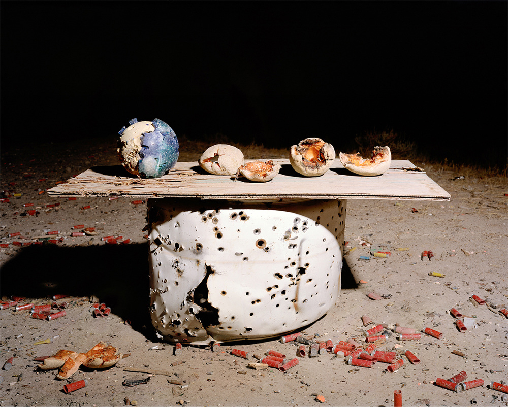 4 cantalopes and a bowling ball are on top of a sheet of wood that sits on a barrel of sorts outside. The bowling ball and catalopes have been destroyed by bullets, as they were used as targets at at shooting range. Red gun cartridges can been seen all over the ground. The photograph appears to have been taken at night but is brightly lit.