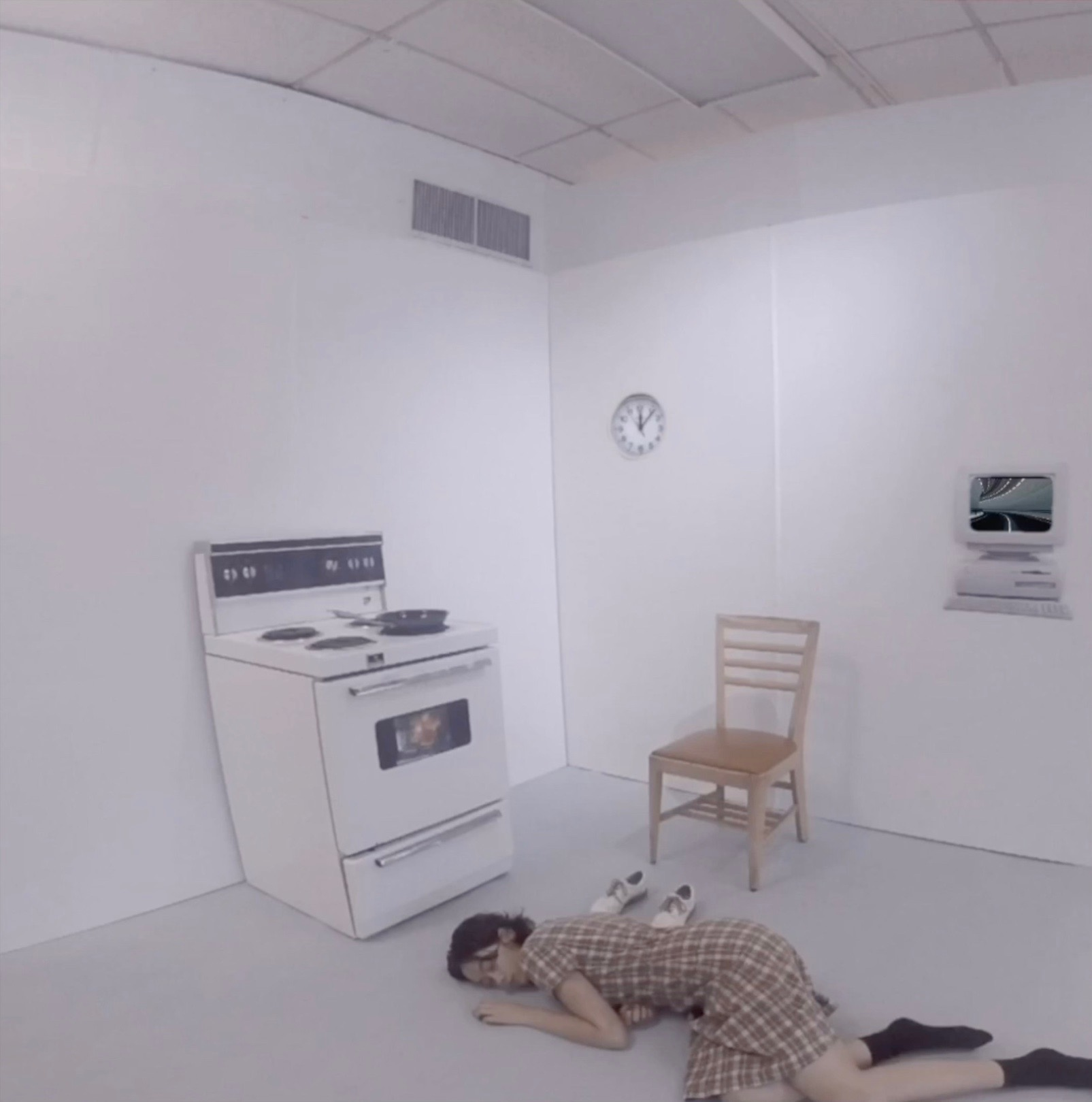 a woman lays on the floor, in an inclosed sterile environment, wearing a plaid dress and black socks, next to her lays a pair of white shoes, a stove and a chair. On the wall hangs a clock and to the right a graphic of a computer.