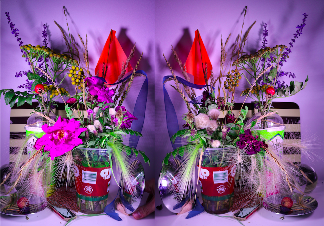 Mirrored image of still life with flowers and leaves in 7-11 Slurpee Cups against a purple background with a small orange flag, a hand in the bottom corner and convex mirror.