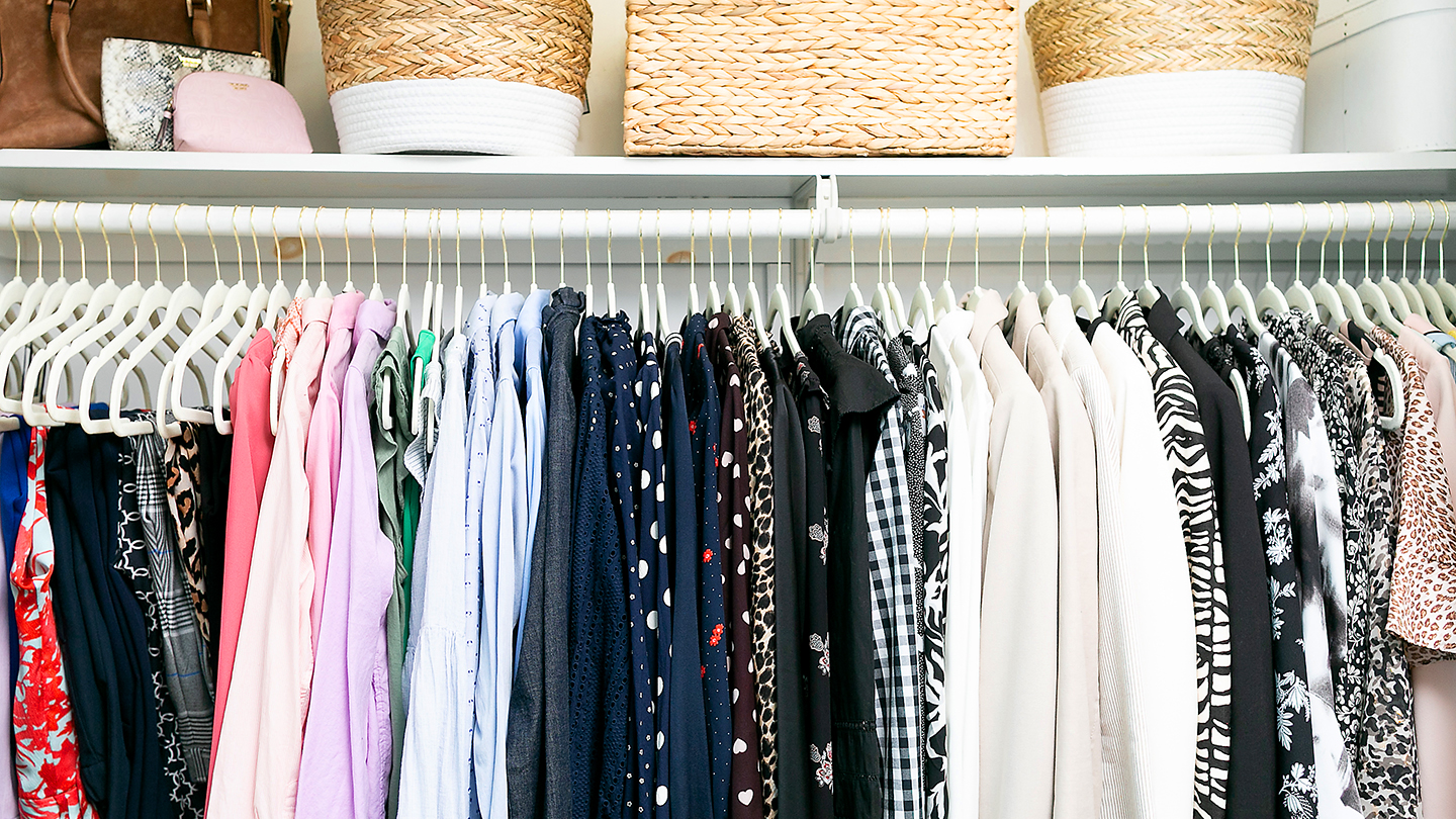 Women's business attire in a closet organized by clothing and accessory style  and color